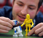 Modelldesigner Stefan Bentivoglio mit den LEGO Star Wars Figuren R2D2 und C3PO