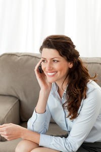 Cheerful businesswoman on the phone sitting on the sofa at home