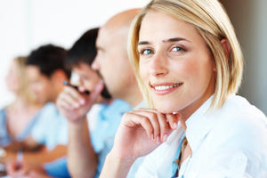 Closeup of a pretty young businesswoman smiling in a meeting with her colleagues in background