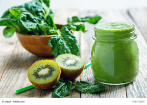 Healthy green smoothie in jar of spinach, kiwi and celery on a wooden table.